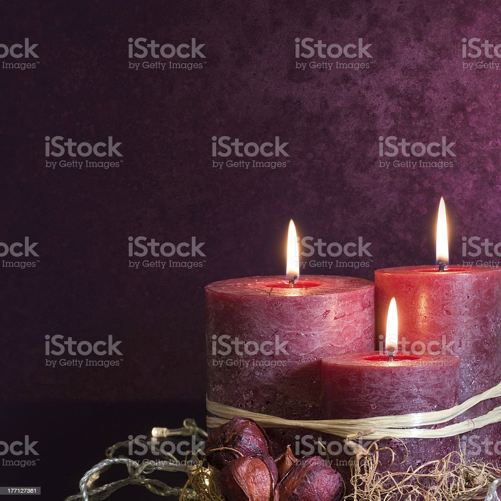 Three candles in purple stock photo