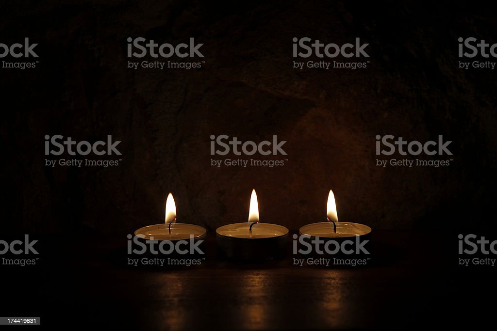 Three candles on a wooden table royalty-free stock photo