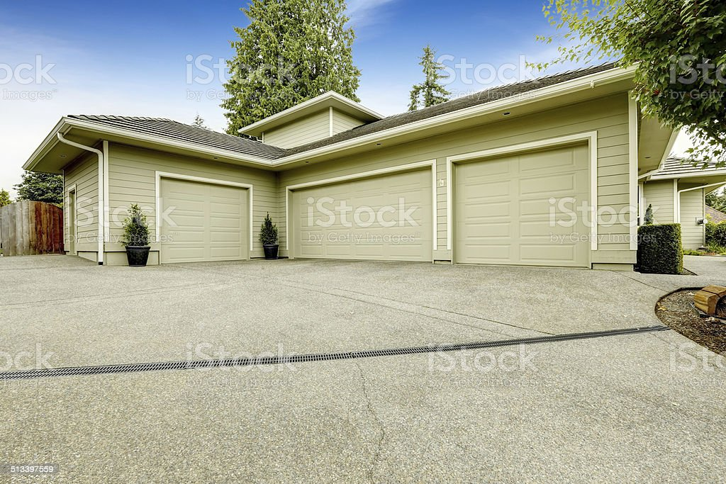 Three car garage with driveway. House exterior stock photo