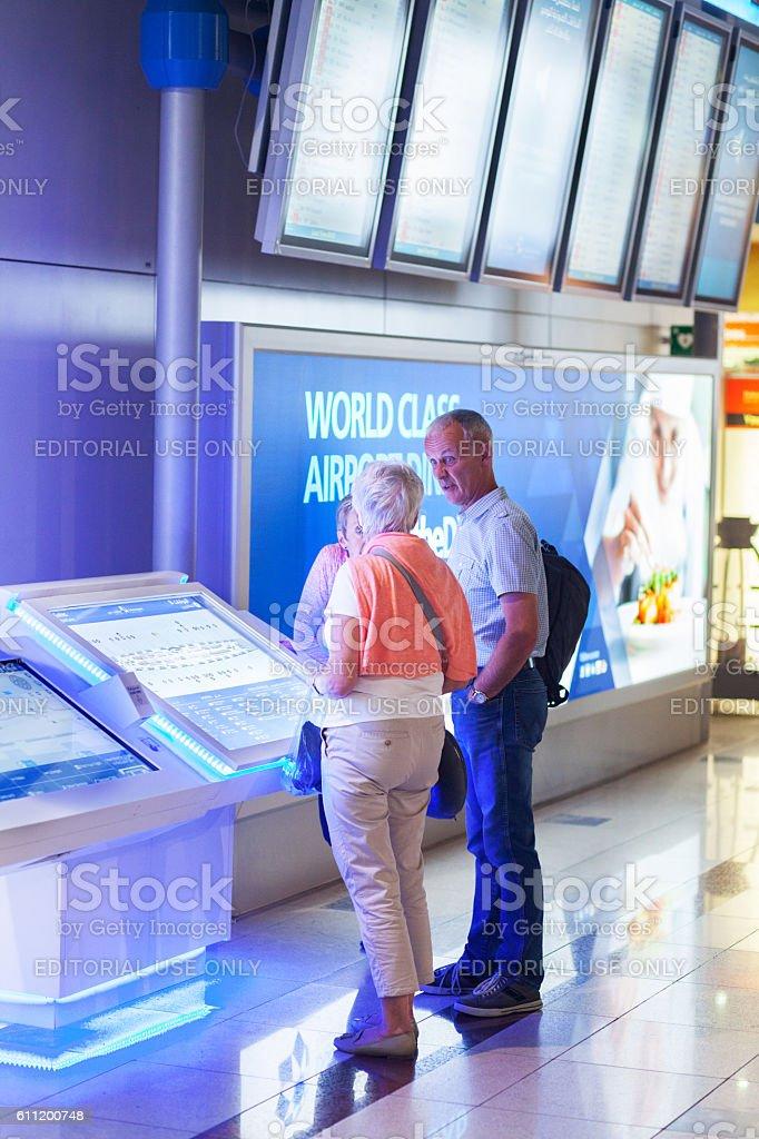 Three caucasian passengers at infomation board stock photo