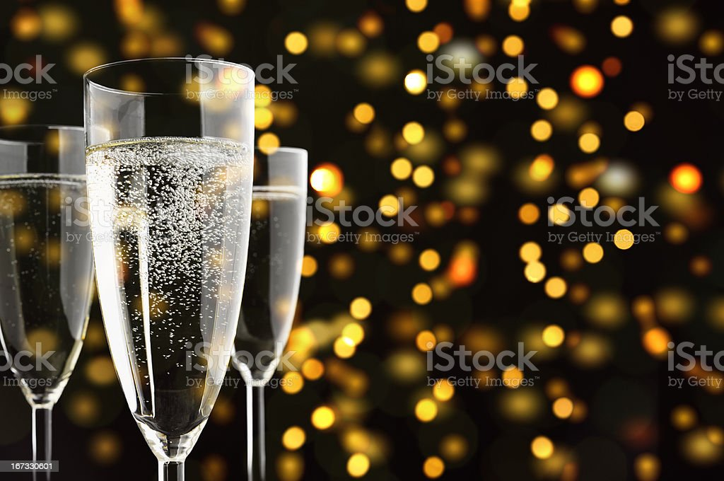 Three Champagne glasses with sparklings, yellow lights in the background stock photo
