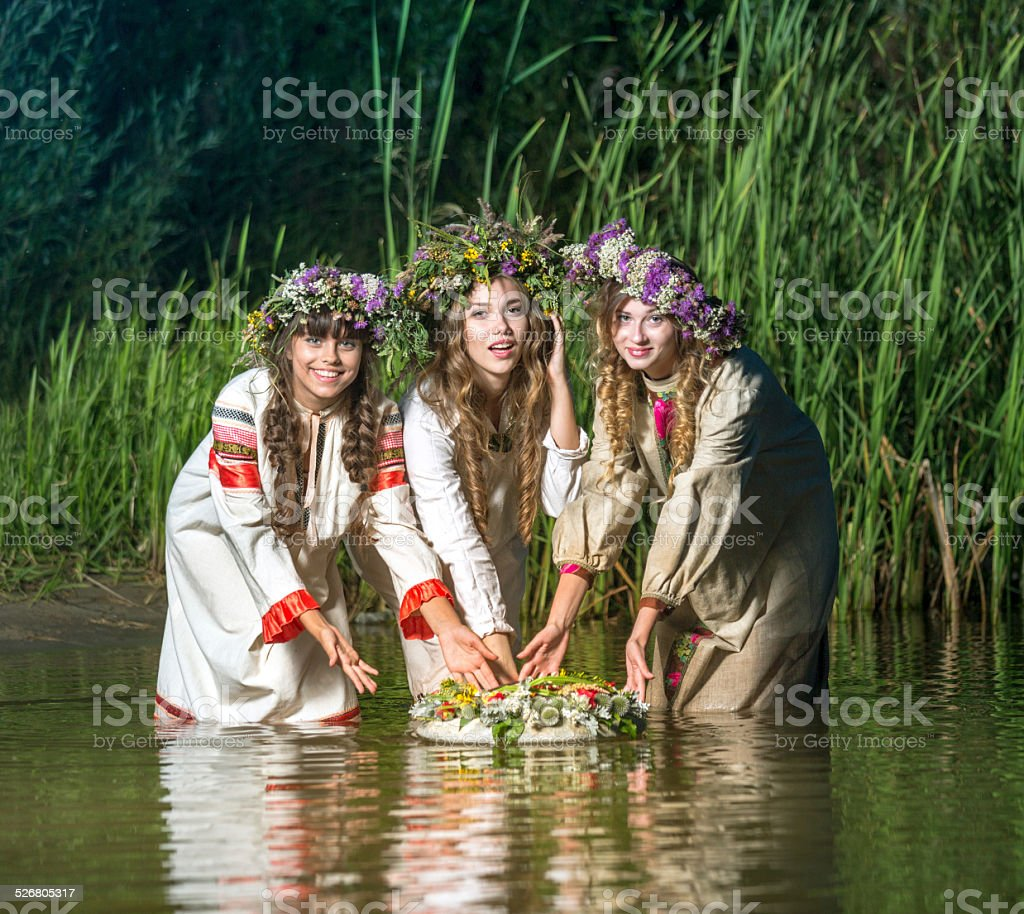 Three charming girls in river at night stock photo