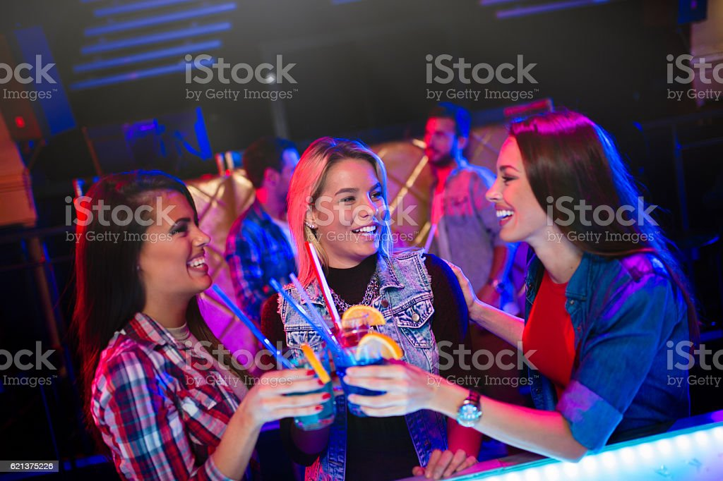 Three cheerful female friends having fun in nightclub stock photo