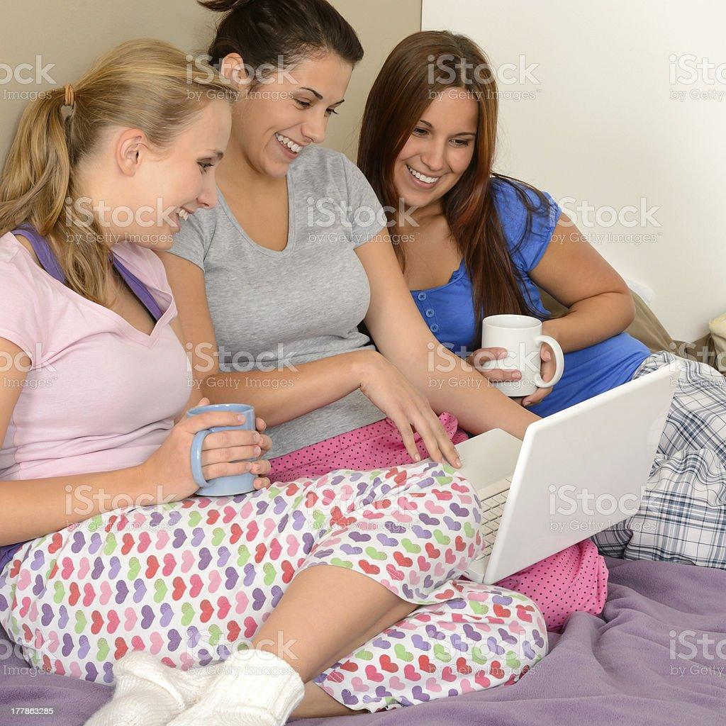 Three cheerful girls surfing on the net stock photo