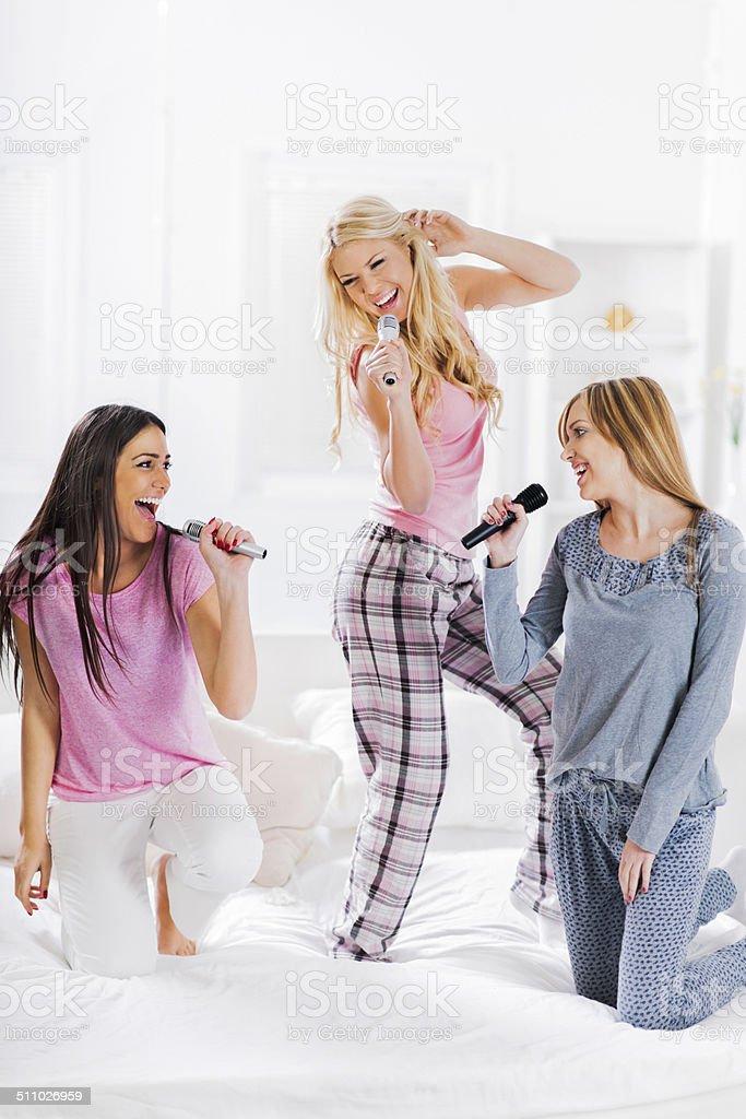 Three cheerful women singing. stock photo