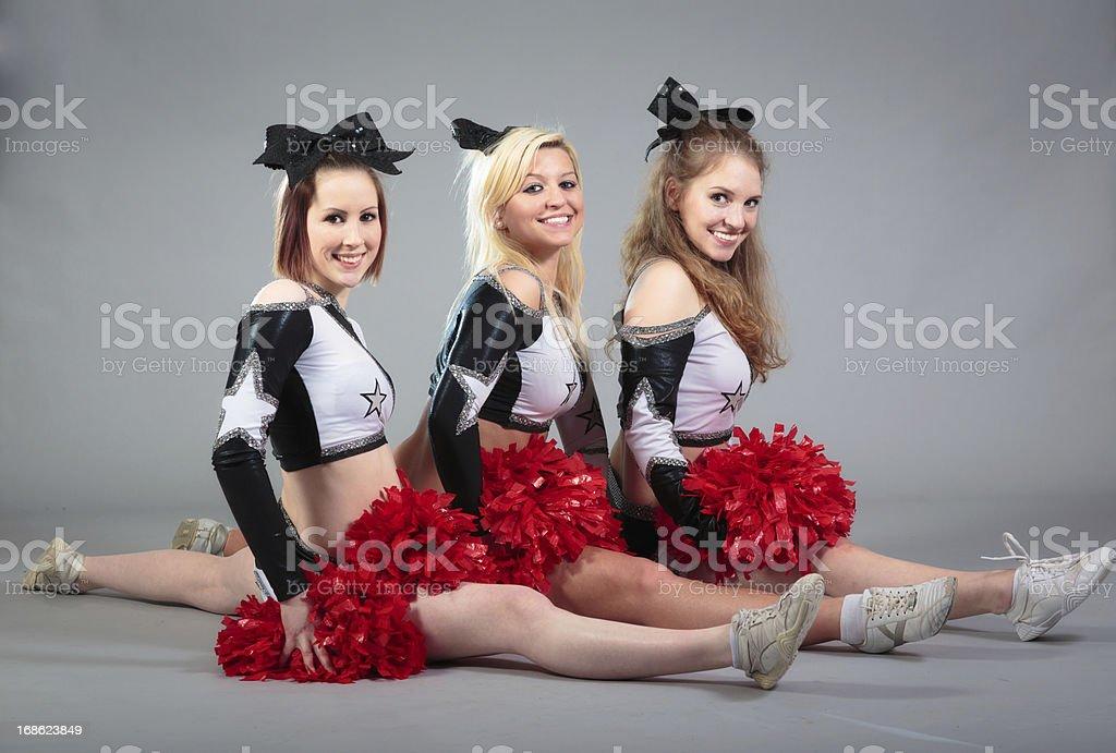 three cheerleaders doing the splits stock photo