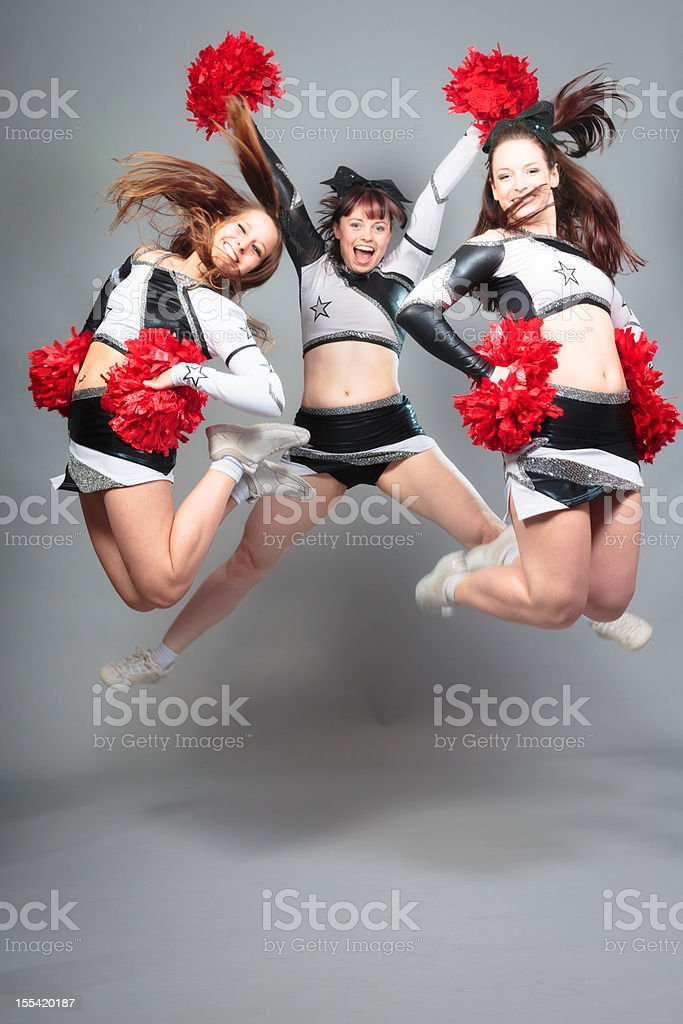 three cheerleaders jumping stock photo
