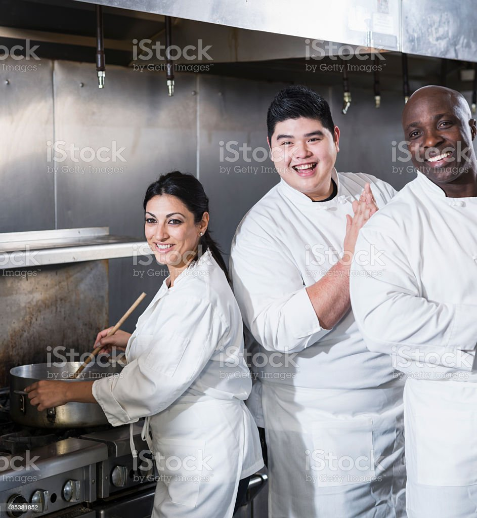 Three chefs working in a commercial kitchen stock photo