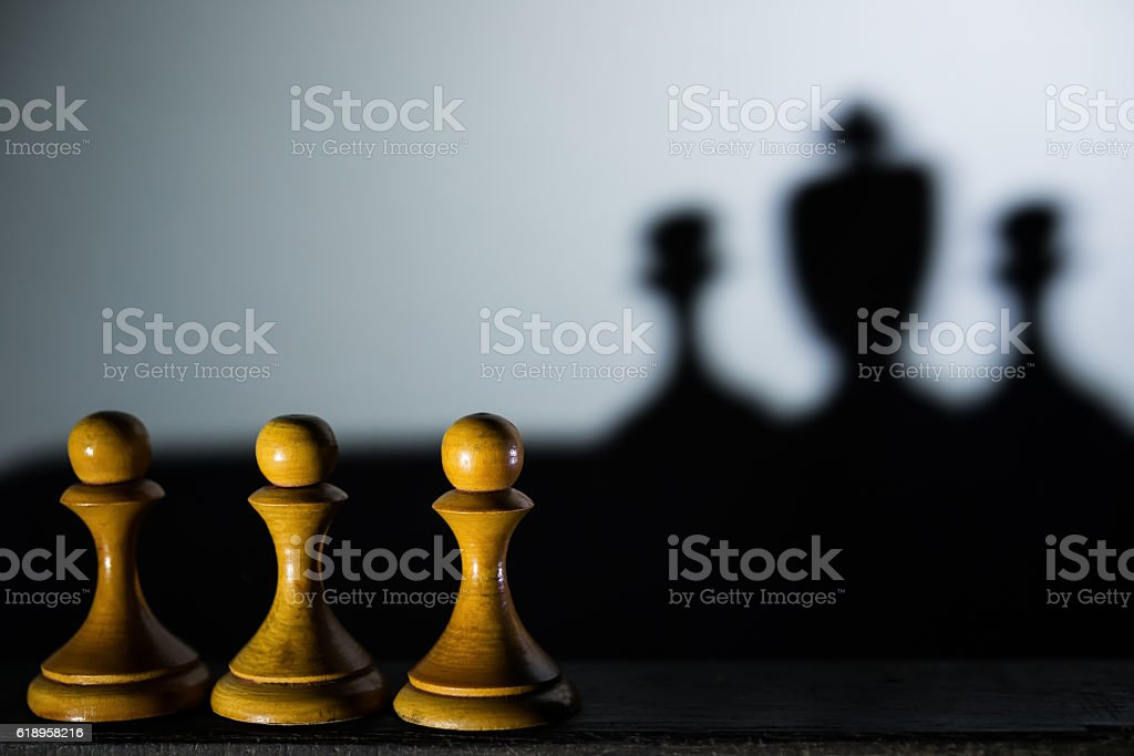 three chess pawn with one casting a king piece shadow stock photo