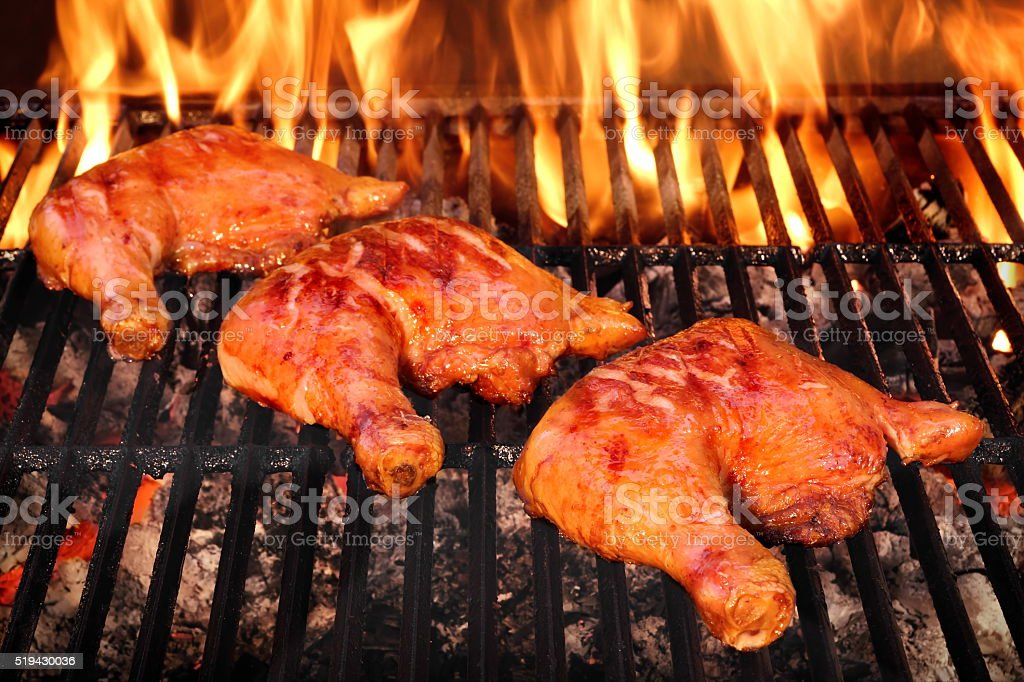 Three Chicken Leg Quarter Roasted On Hot BBQ Flaming Grill stock photo