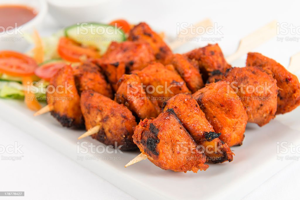 Three chicken tikka kebabs on a fancy plate stock photo