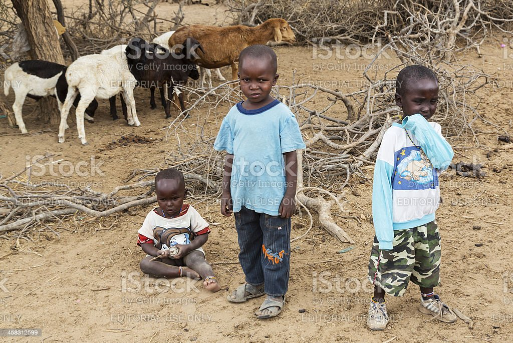 Three children and goats in Maasai village. royalty-free stock photo