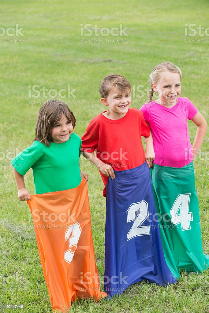 Three children doing sack races in the park stock photo