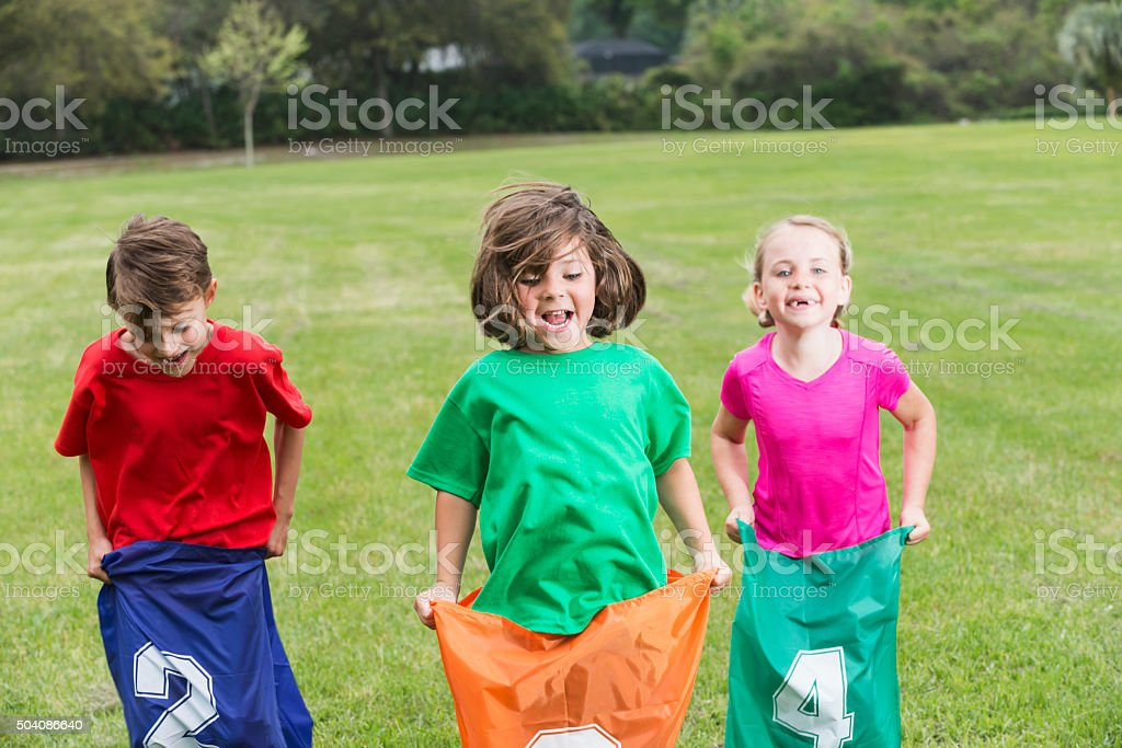 Three children having fun competing in potato sack race stock photo