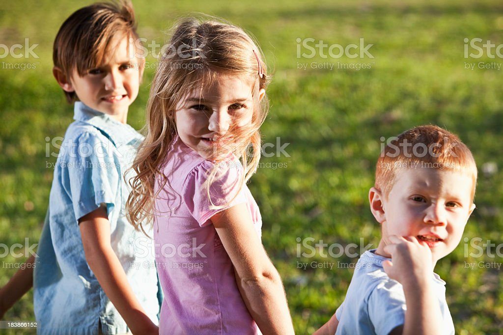Three children holding hands at the park royalty-free stock photo