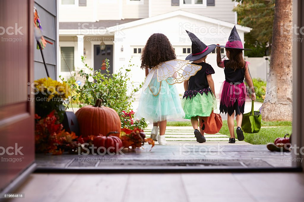 Three Children In Halloween Costumes Trick Or Treating stock photo