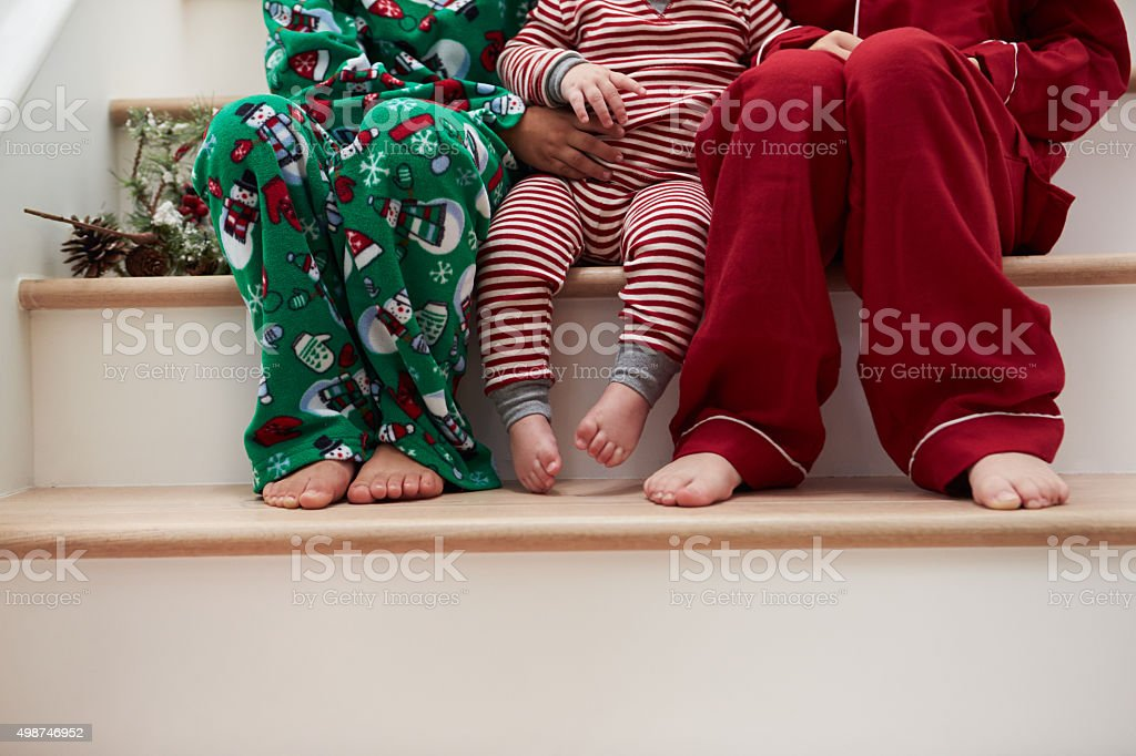 Three Children In Pajamas Sitting On Stairs At Christmas stock photo