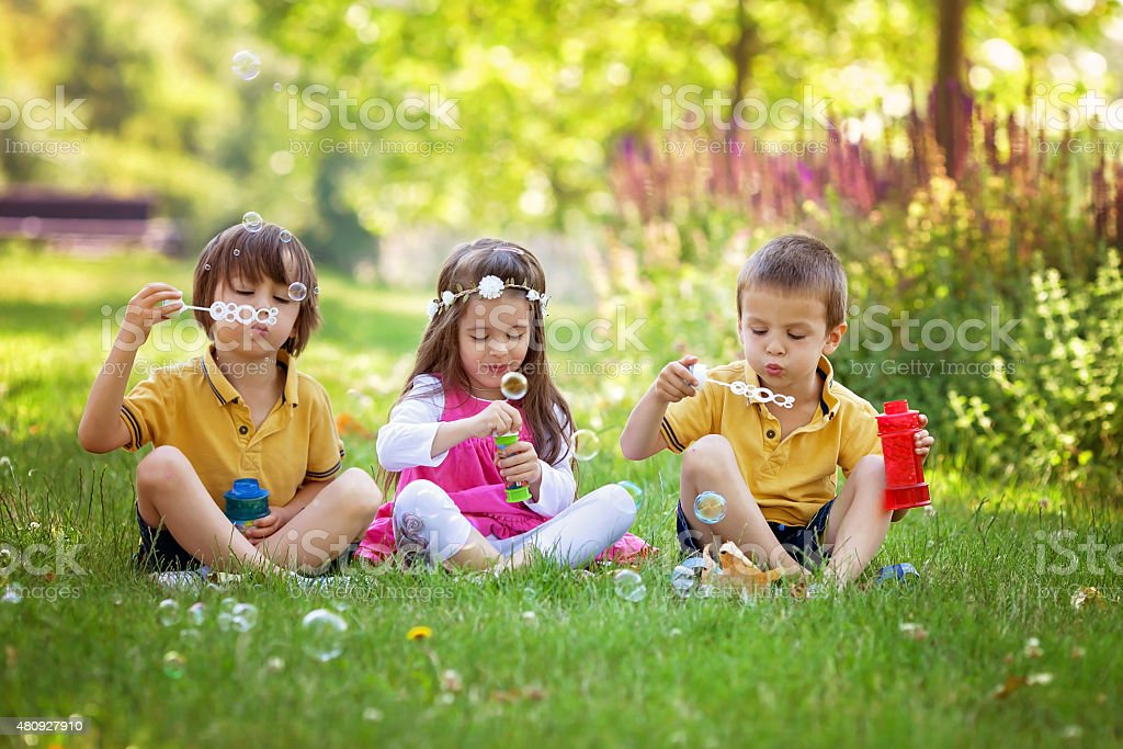 Three children in the park blowing soap bubbles stock photo