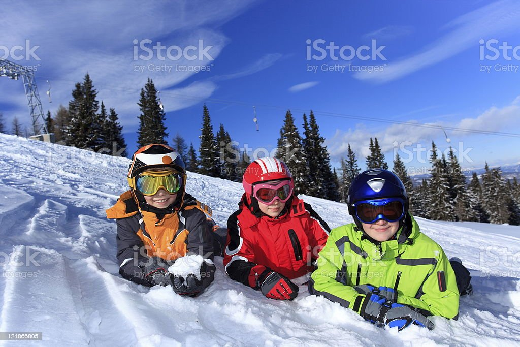 Three children in winter gear lying in the snow stock photo
