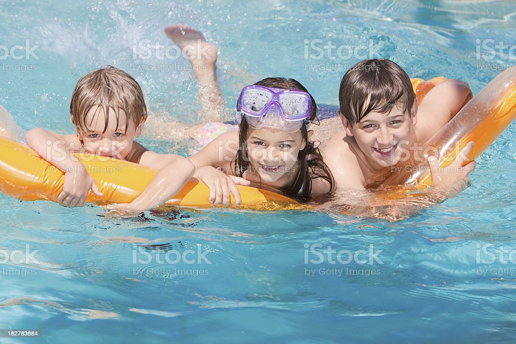 Three Children Playing on a Float in the Swimming Pool royalty-free stock photo