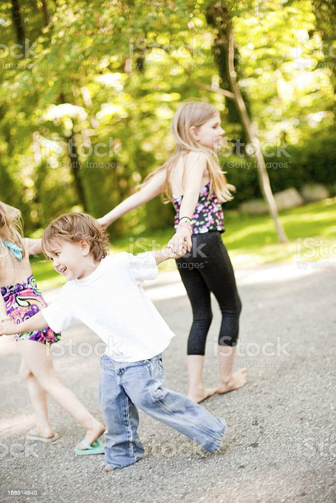 Three Children Playing Together While Holding Hands royalty-free stock photo