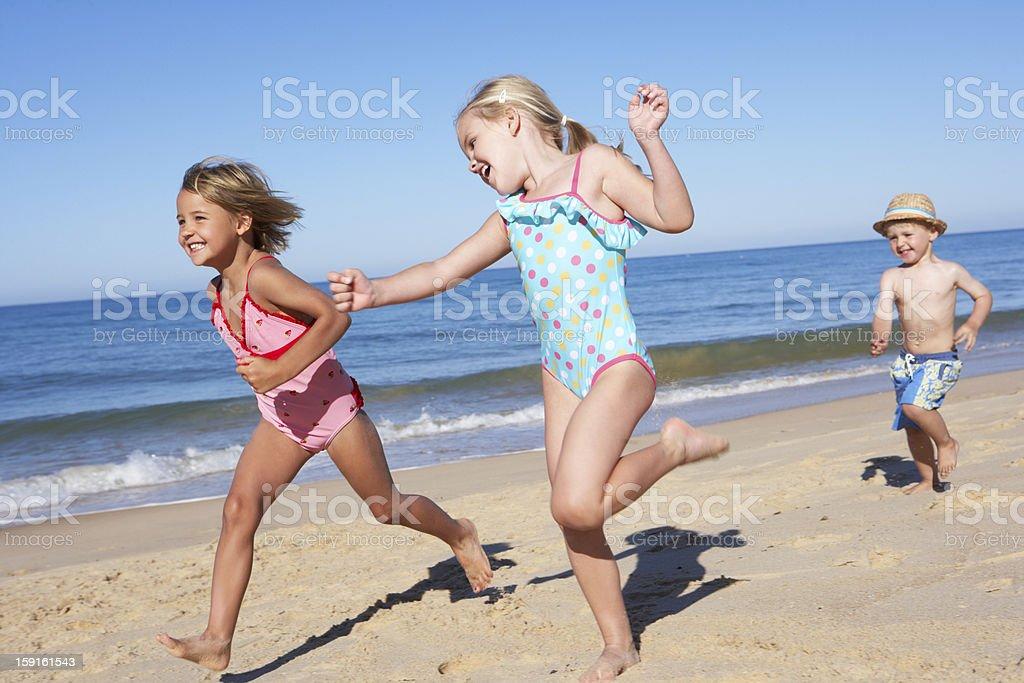 Three Children Running Along Beach royalty-free stock photo