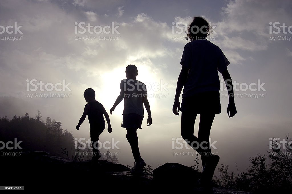 Three Children Walk Toward a Bright Future stock photo
