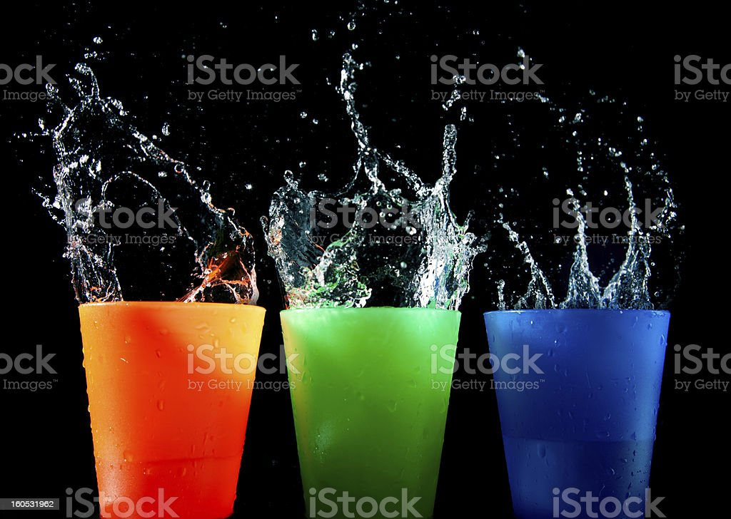 Three Children's multicolored plastic cups with splashes royalty-free stock photo