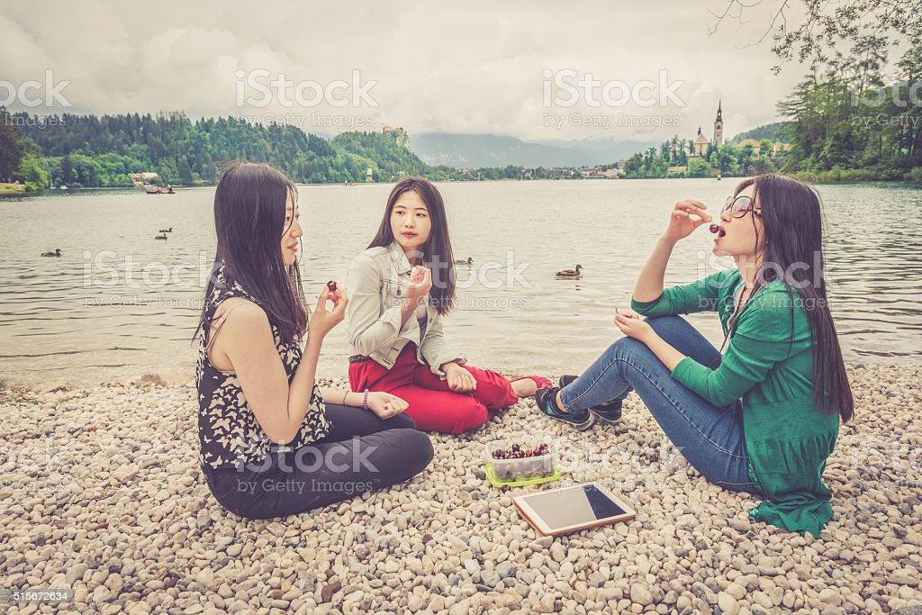 Three Chinese Friends Eating Cherries by Bled Lake, Slovenia, Europe stock photo