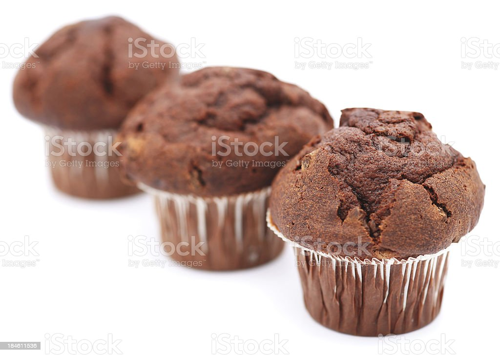 Three chocolate muffins in a row isolated on white royalty-free stock photo