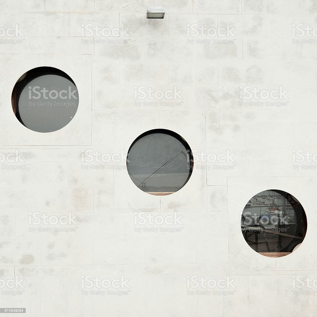 Three circular windows in a concrete wall stock photo