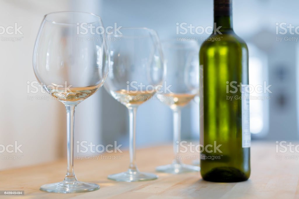 Three clear wine glasses and a bottle of chilled white wine on a wooden table stock photo
