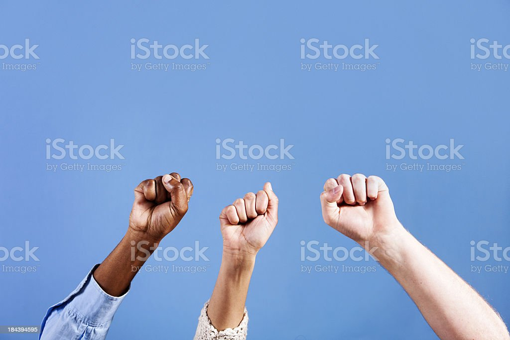 Three clenched fists punch the air against blue background royalty-free stock photo