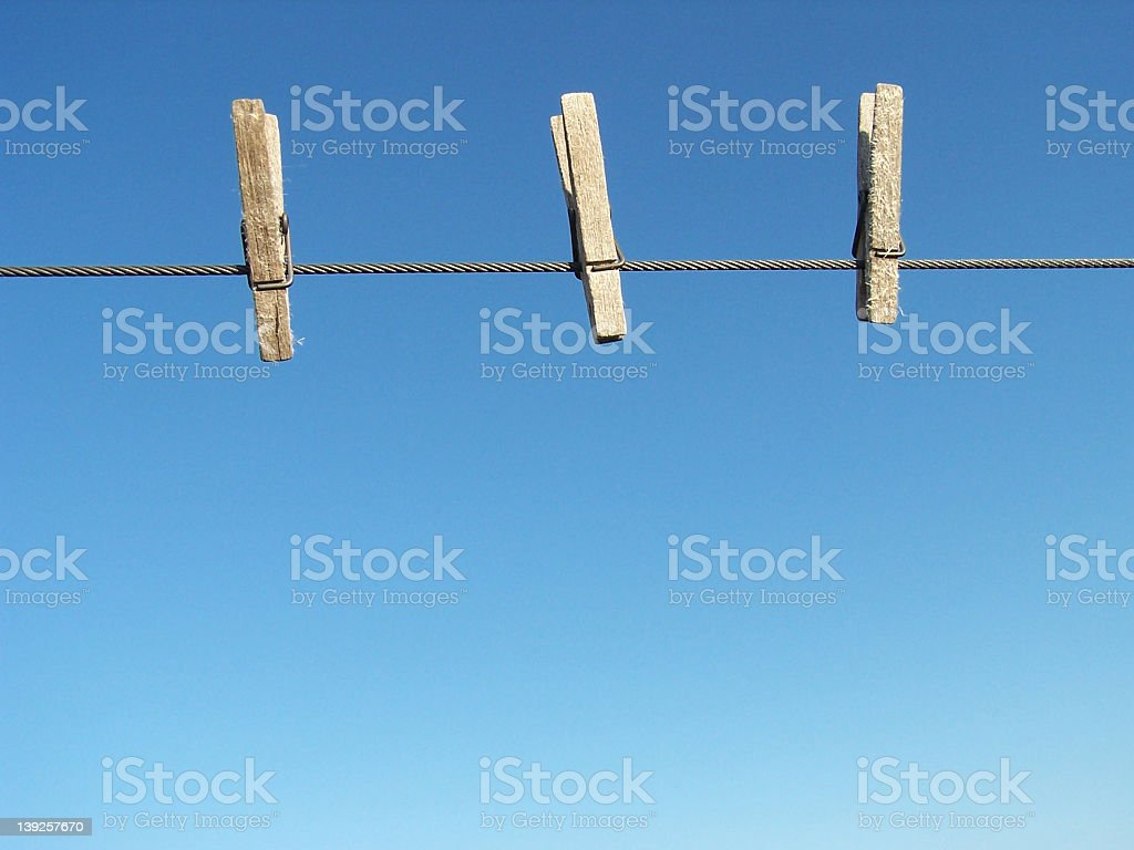 Three clothes pins on a clothes line royalty-free stock photo