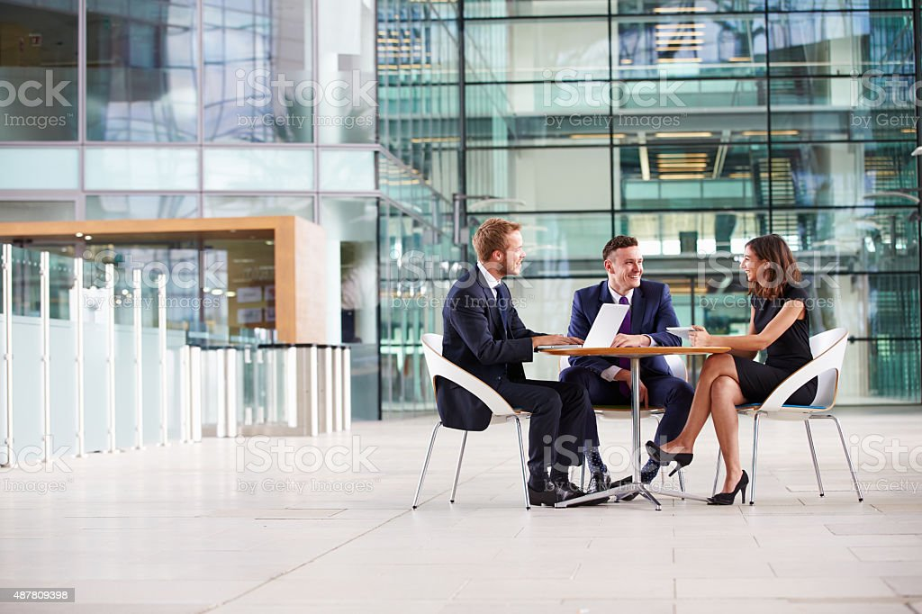Three colleagues at a meeting in the foyer of business stock photo