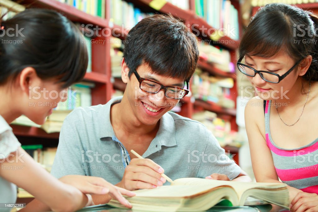 three college students study in the library royalty-free stock photo