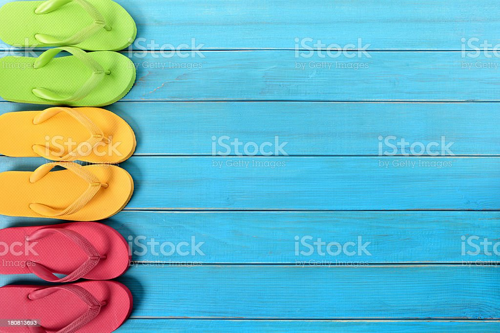 Three colored sets of flip flops on a blue wood deck stock photo