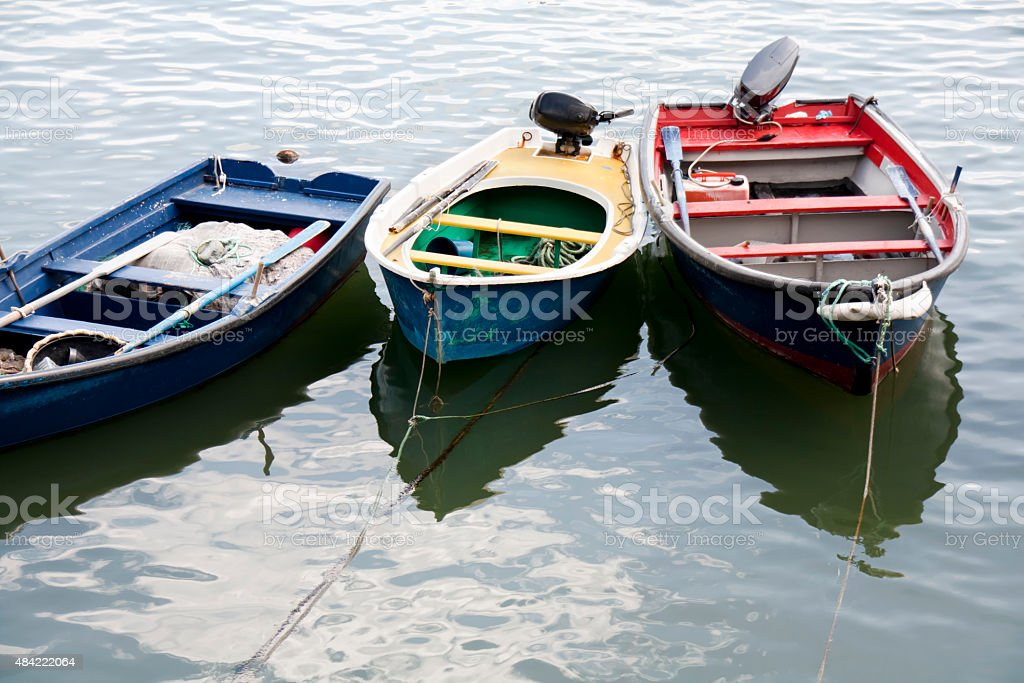 Three colorful boats mooring in a fishing harbor . stock photo