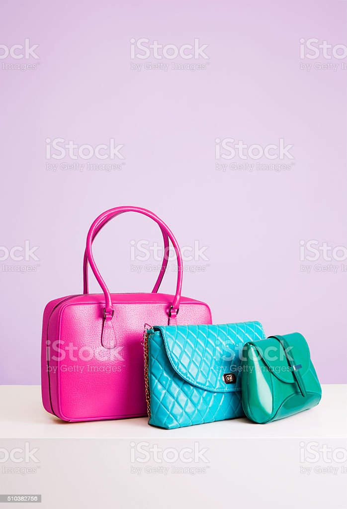 Three colorful leather bags and purses. Isolated on purple background. stock photo