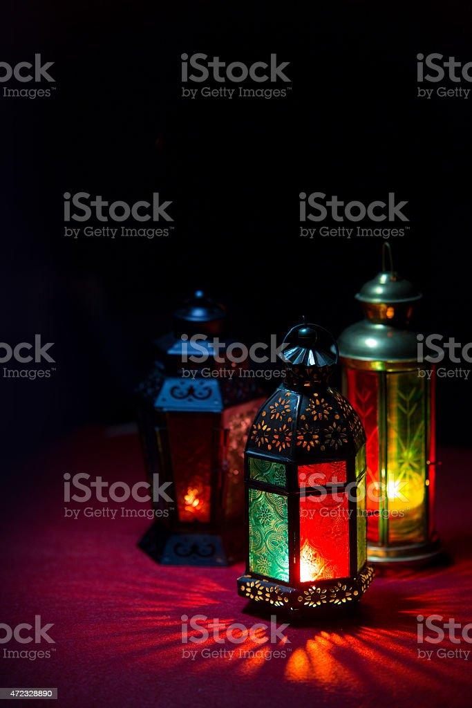 Three colorful Ramadan lanterns lightening up dark space stock photo