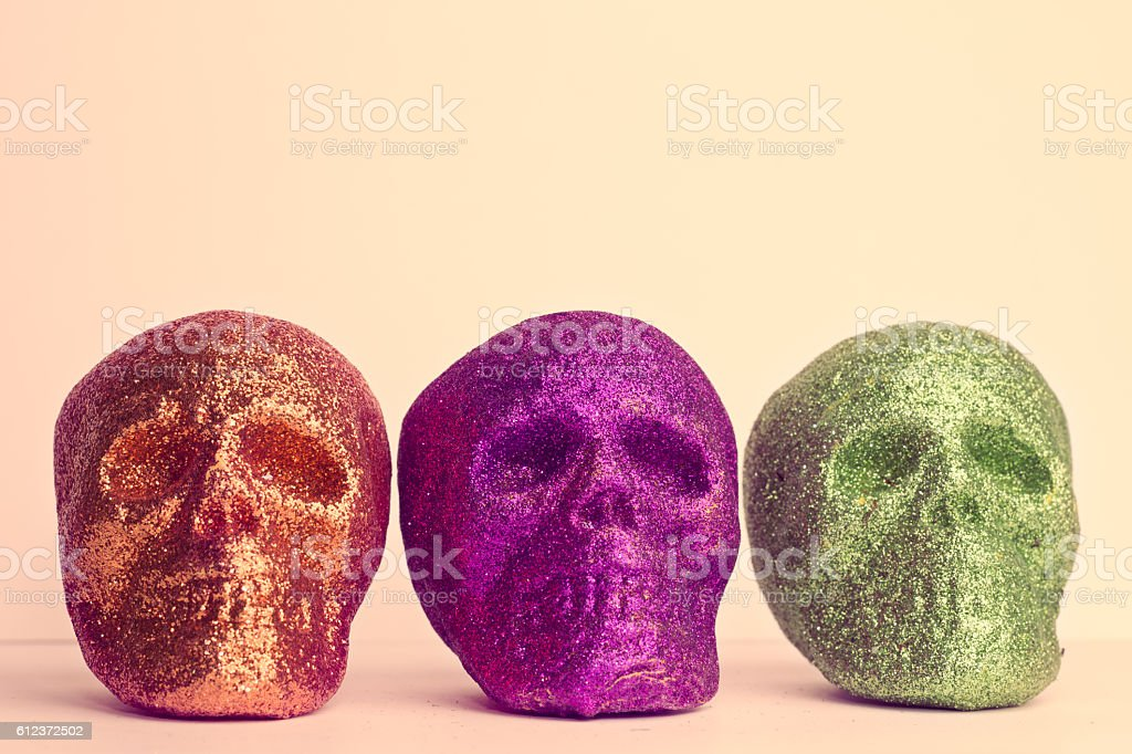 Three Colorful Skull Heads on Pink Background stock photo