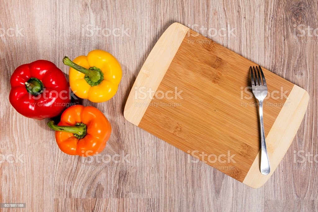 Three colors the peppers on wood cutting background with fork. stock photo