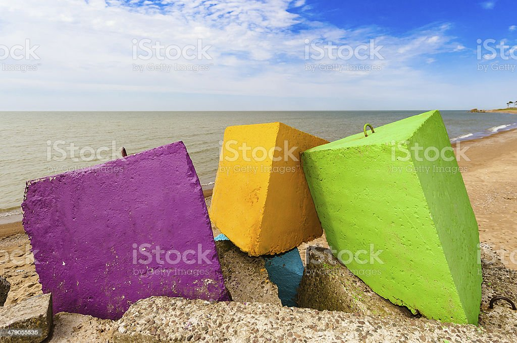 Three colourful blocks of a concrete breakwater by the sea. stock photo