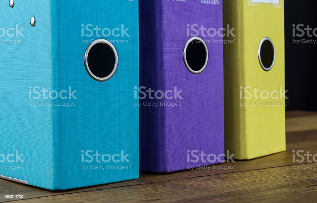 Three colourful lever arch files on a desk stock photo
