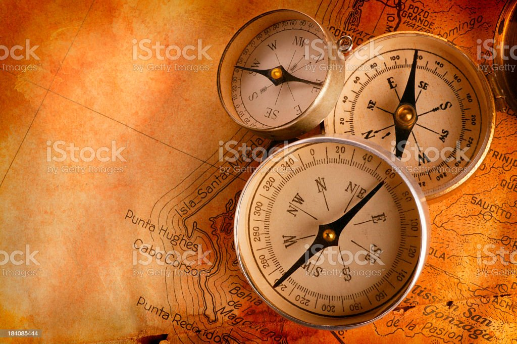 Three Compasses Leaning On One Another On Old Antique Map stock photo