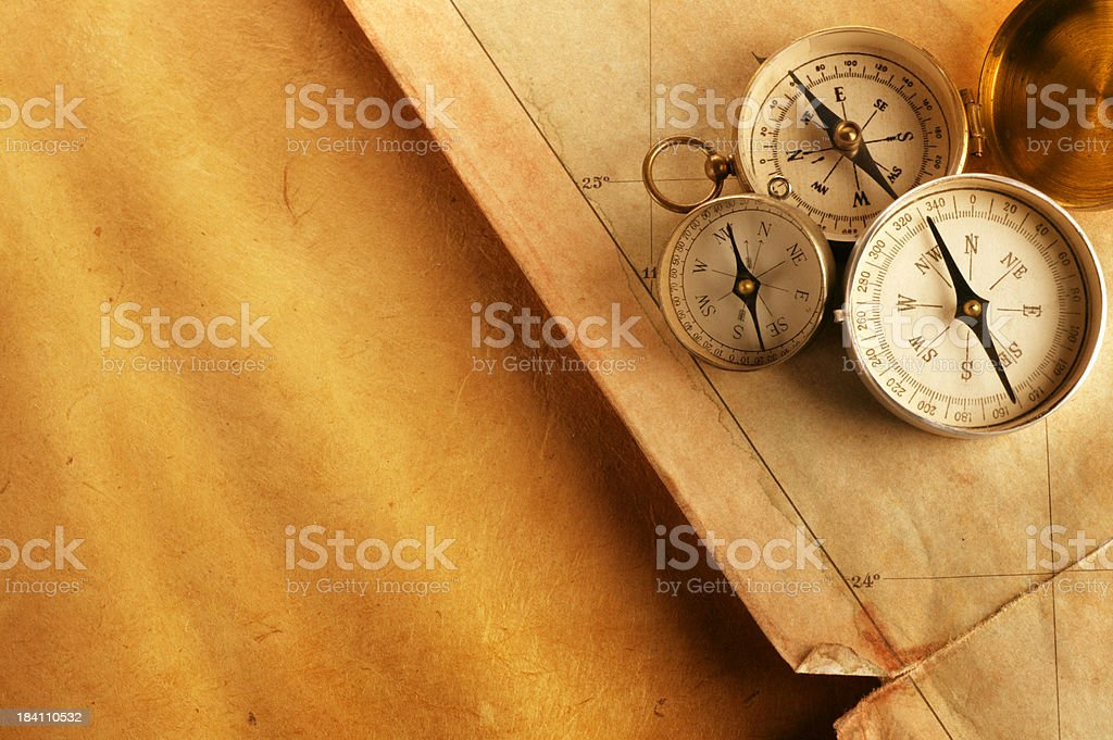 Three Compasses On Old Tattered Map Sitting On Golden Paper royalty-free stock photo