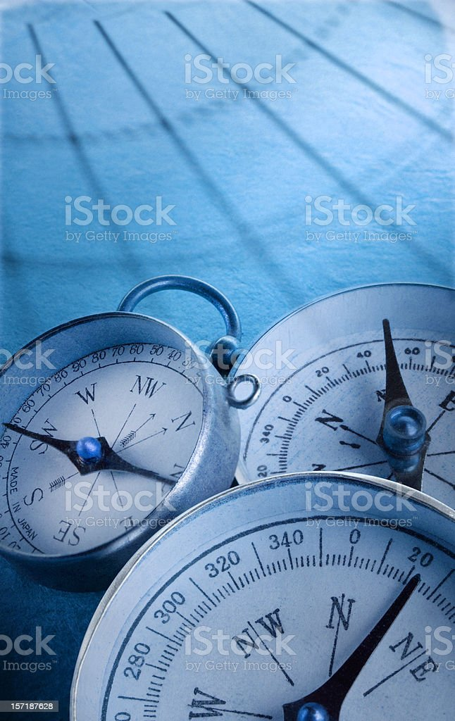 Three compasses with blue grid of latitude and longitude lines royalty-free stock photo