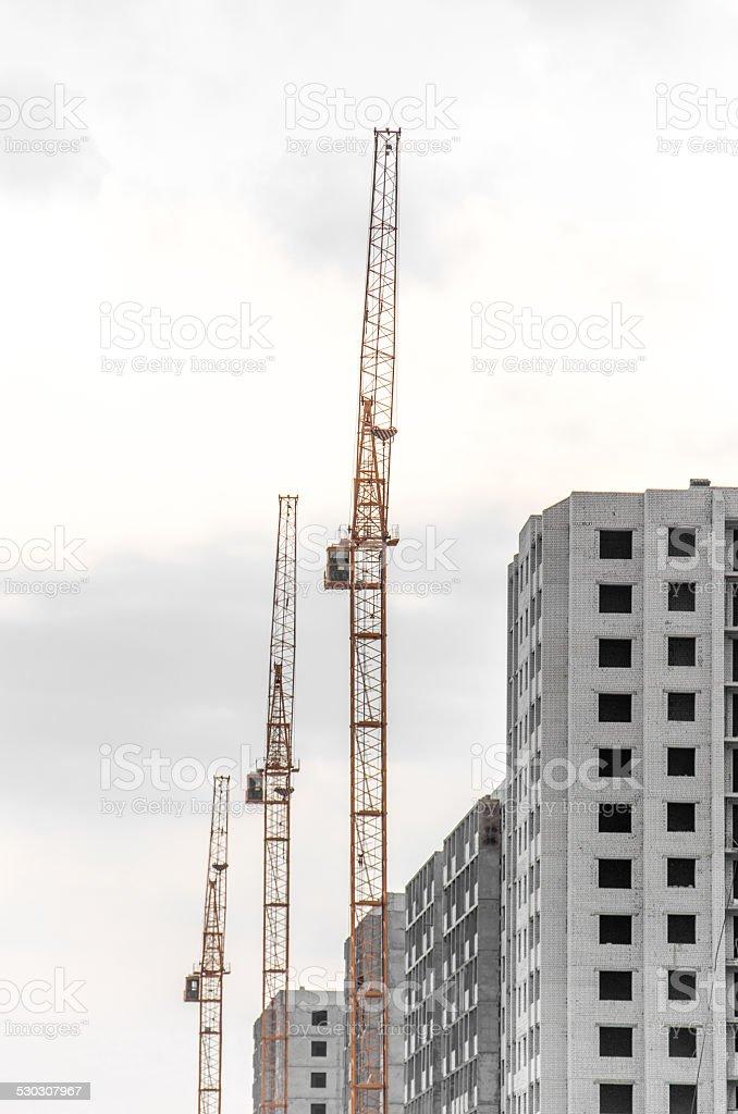 Three Construction crane on a cloudy sky stock photo
