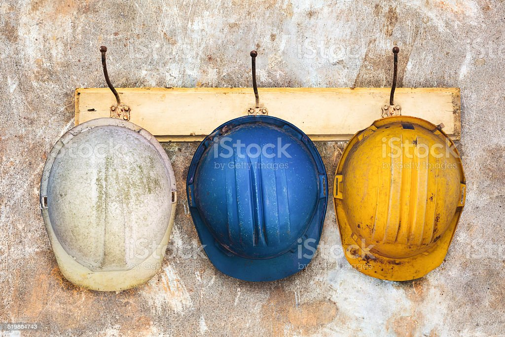 Three construction helmets hanging on a hat-rack stock photo