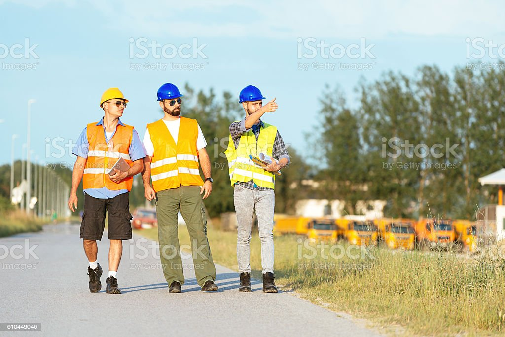 Three construction workers or engineers on construction site stock photo
